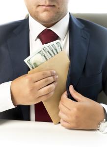 businessman hiding envelope with money in pocket at jacket